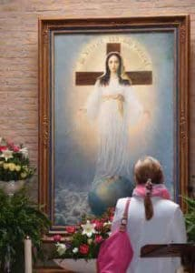 Praying before the image of Our Lady of All Nations in Amsterdam