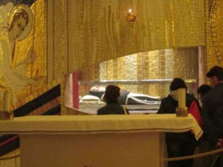 Praying before the incorrupt body of Saint Padre Pio