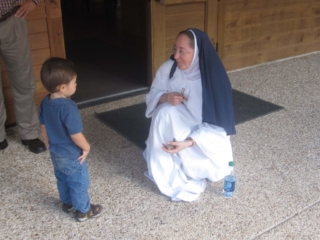 Sister Ampola meets one of our young visitors to the Divine Mercy Center