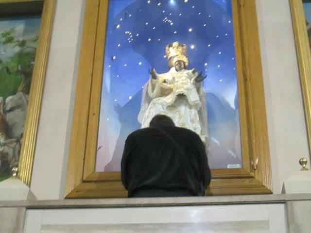 Praying before the image in the Shrine of BVM Mother of God Crowned in Foggia