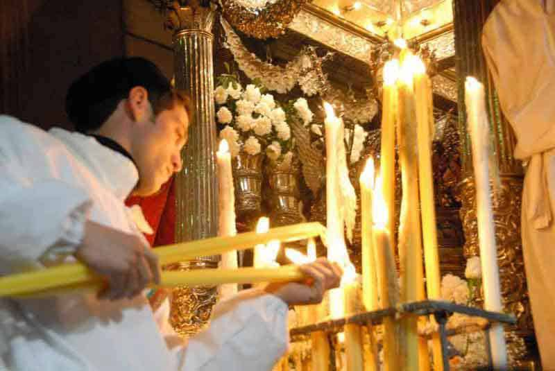 Lighting candles at the tomb of Saint Agatha